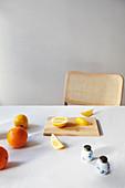 Zitronen und Orangen, ganz und aufgeschnitten auf Tisch