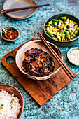 Braised Pork Belly with Smashed Cucumber Salad, Steamed Rice, Chili Oil and Sesame Seeds