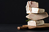 Various lardo pieces stacked on a wooden board