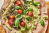 Avocado-Wrap mit Oliven, Kirschtomaten und Sesam