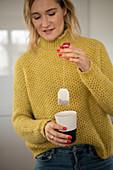 Blonde woman holds a tea bag in a mug