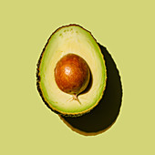 Halved avocado on green background
