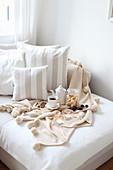 Holzbrett mit Tee, Keksen und Schokolade auf Bett