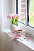 Vase with bouquet of tulips and teacup on windowsill