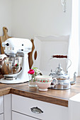 Tea kettle, tea cups and a small bouquet of flowers next to the food processor