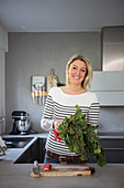 Blonde woman with a bunch of rhubarb in a kitchen
