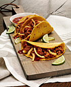 A cutting board with three Adobo Pork Tacos in corn tortillas with lime slices garnish