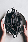 Vanilla beans in bowl with hands