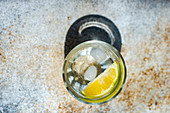 Heathy water with lemon and ice on concrete table in sunny day