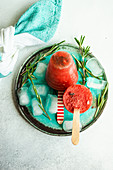 Summer dessert with organic watermelon popsicles served on plate with ice and rosemary
