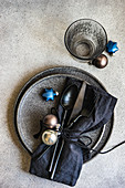 Minimalistic table setting with black stoneware and Christmas decoration on grey concrete background