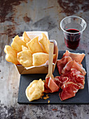 Gnocco fritto (bread made of flour, water and lard, Emilia Romagna, Italy) served with ham and red wine