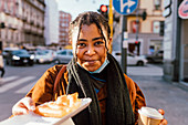 Portrait of smiling woman with snack on street, Italy