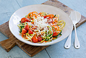 Mixed vegetable noodles of zucchini, summer squash, and carrots with grated cheese and tomatoes