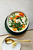 Fish soup with beans, carrots and spinach