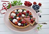 Vegan summer berry tart with coconut-mango filling and cherry glaze