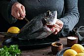 Woman chef preparing a fresh fish dorado by cutting