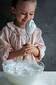 Little smilling girl prepares whipped cream and tastes it straight from the whisk