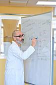 Teacher explaining chemistry on a whiteboard