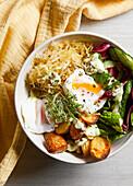 Sauerkraut bowl with poached eggs, avocado and kefir