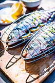 Fresh trout with lemon and herbs in the fish grilling baskets
