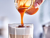Pouring caramel sauce over a vanilla macchiato