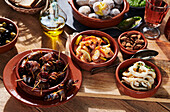 Tapas - dates wrapped in bacon, prawns, boiled potatoes, and squid