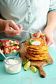 Vegetarian corn pancakes with an avocado and radish salad