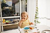 Toddler girl eating at table