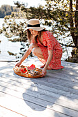 Woman putting tray with food on jetty