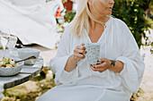 Woman in garden holding mug