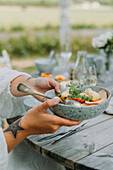 Woman's hands holding a bowl of potato and apple salad