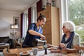 Home carer preparing coffee break for senior woman