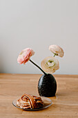 Persian buttercup flowers in vase and cinnamon bun on plate