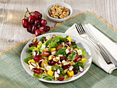 Fruity salad with lettuce, mango, grapes, goat's cheese and walnuts