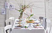 A bouquet of flowers on a spring table laid with appetizers