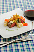 Beef tenderloin Tournedos with potato sticks, fine herbs, and cauliflower sprinkled with poppy seeds