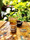 A glass of mint tea and a bowl of brown sugar on a tray in the garden