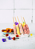 Raspberry and apricot ice cream on a stick