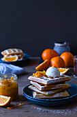 Orange syrup waffles served with vanilla ice cream and orange marmalade