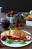 Butter croissant with strawberries and basil leaves