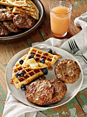 Beef breakfast sausage patties with waffles, blueberries, butter and maple syrup, a glass of grapefruit juice
