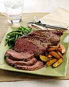 A beef Tri Tip roast with roasted potato wedges and green beans
