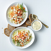 Salmon salad with apples, croutons and horseradish cream on white cabbage
