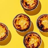 Pastel de Nata Fresh baked Portuguese egg custard Tart on yellow background