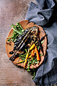 Grilled cooked fresh gutted sea bream on ceramic plate wrapped in bamboo leaves served with herbs, colorful carrots