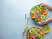 Quinoa Buddha Bowl with chopsticks on a blue background