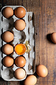 Chicken eggs in a cardboard carton with one cracked egg.