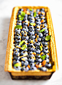 Blueberry tart with mint and almonds on a white, marble countertop