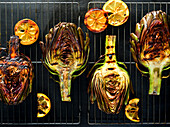Grilled artichokes and lemons on a cooling rack over a dark, moody surface.